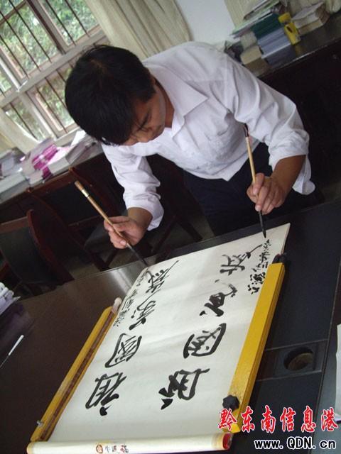 写,右手写正字,左手写反字,运笔自如.图为江老师在国庆期间向