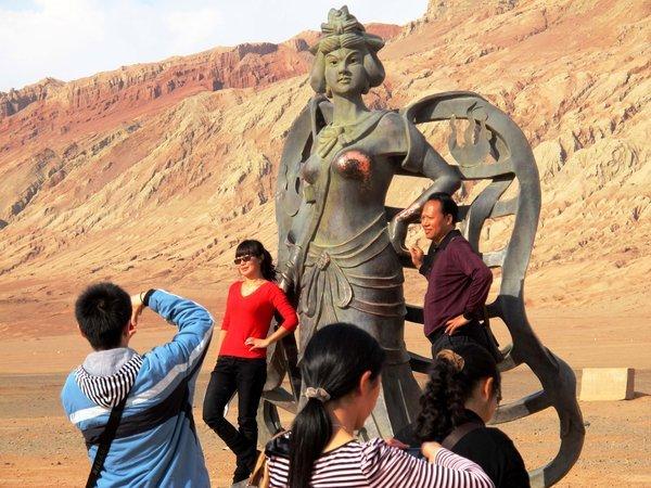 """火焰山风景区,两名游客攀爬上已经衣不遮体的""""铁扇公主""""雕塑拍照留念."""